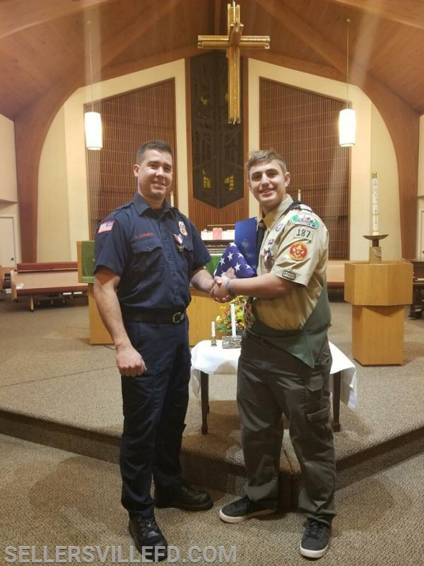 Firefighter Doug Cesmegi congratulating Eagle Scout Andreas Skoufos.