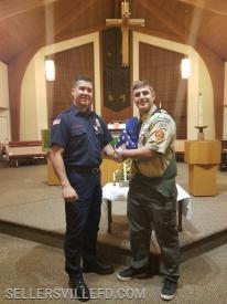 Firefighter Doug Cesmegi congratulating Eagle Scout Andreas Skoufos.