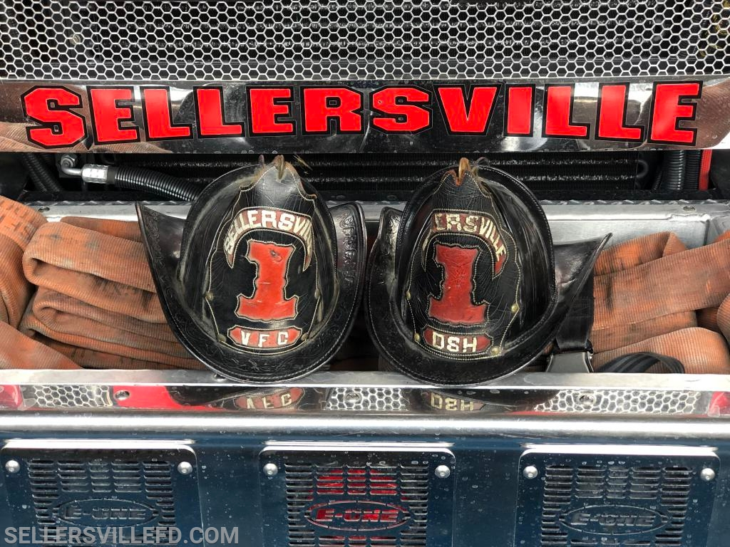 A pair of antique Sellersville helmets. The Helmet on the right is in honor and memory of Past Chief Harry McElhare, Sr.
